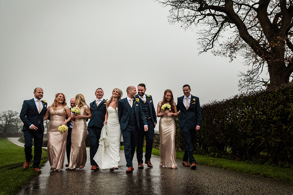 Metallic pink bridesmaid dresses and navy woollen three-piece suits contrast beautifully at this rustic winter wedding at Sandhole Oak Barn in rural Cheshire