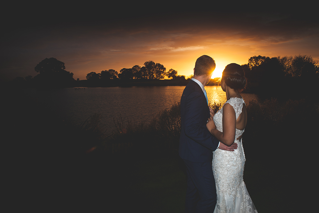 The bride and groom pose for a wedding photo at this beautiful waterside wedding venue near Manchester