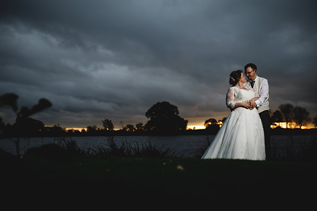 The bride and groom pose for a photo by the lake at this beautiful barn venue in Cheshire