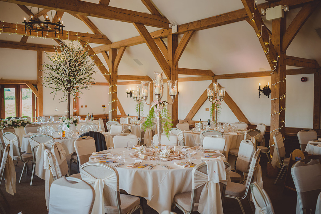 The Oak Barn was set up for the wedding breakfast with tall candelabras as centrepieces at this barn wedding