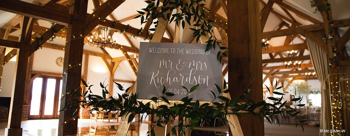 A pretty wedding sign surrounded by lovely greenery welcomed guests to the wedding reception at this wedding barn in Cheshire