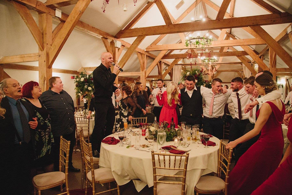 The wedding guests enjoy a sing-song at this winter wedding at Sandhole Oak Barn