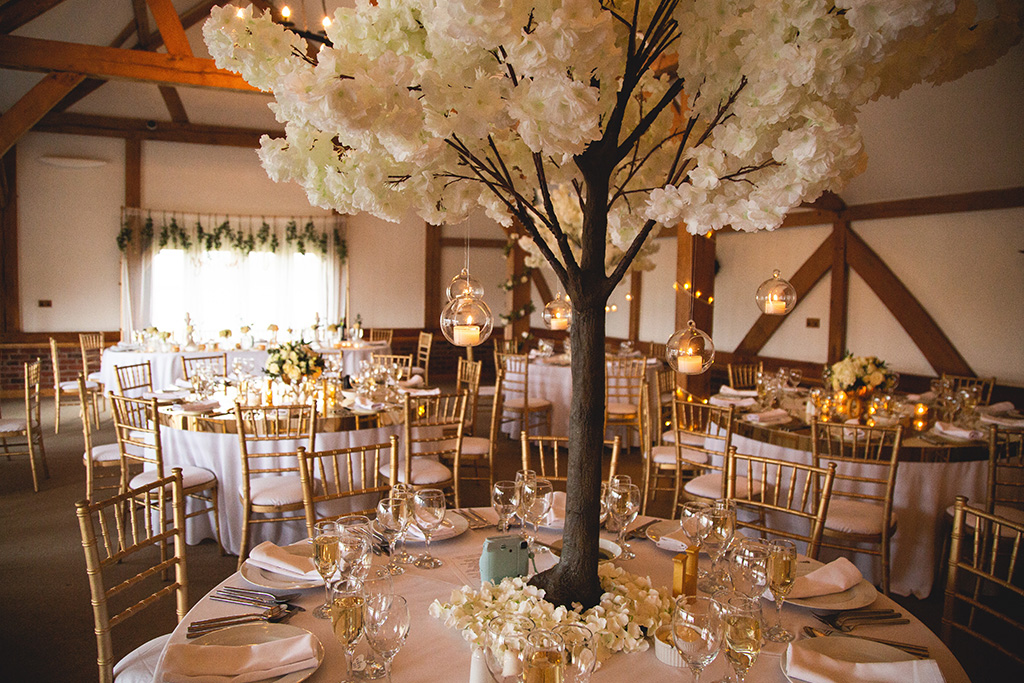 Decorate tables with gold tea light holders and mini blossom trees adorned with candle baubles for that perfect autumnal wedding look