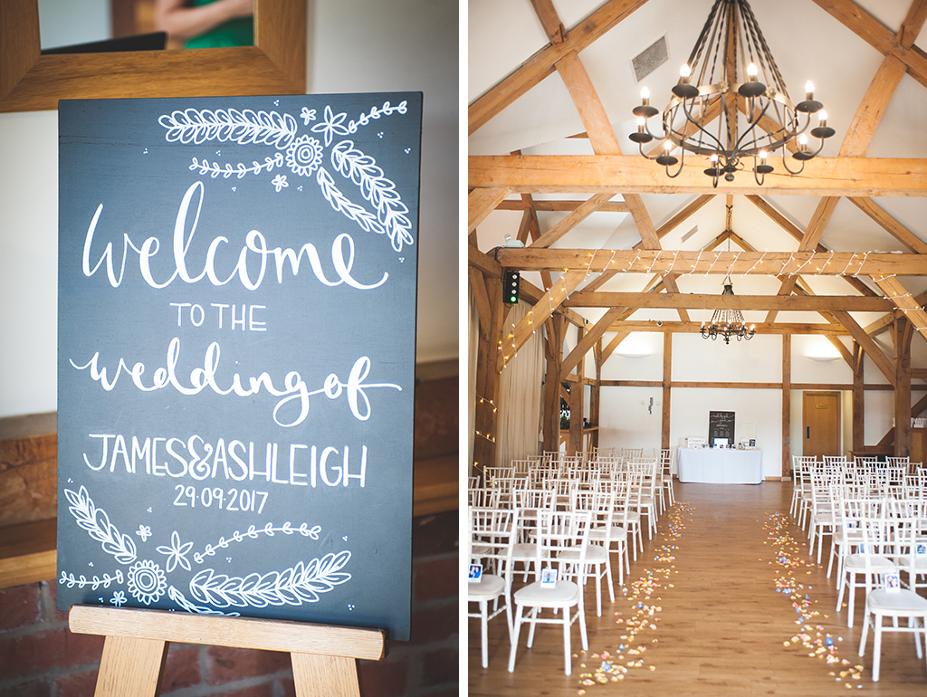 A pretty chalk board sign welcomes wedding guests and the wedding aisle is lined with pretty scattered petals at this barn wedding near Manchester