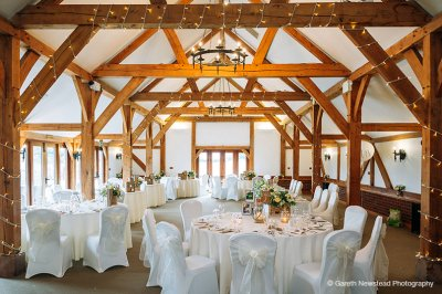 The barn wedding was simply but effectively decorated with fairy lights on the beams, white covers and sashes on the chairs and lanterns and tealights on the tables.