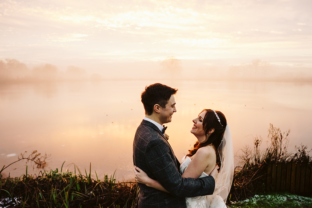 The happy couple pose for a wedding photo by the lake on their winter wedding day at Sandhole Oak Barn