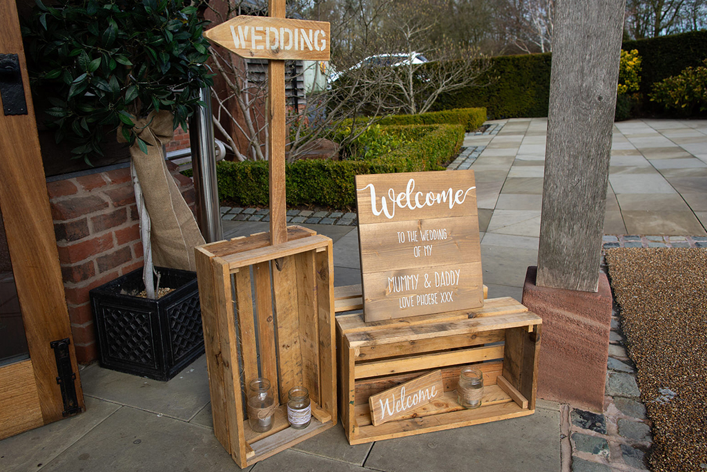 The couple chose wooden crate wedding signs for their barn wedding in Cheshire
